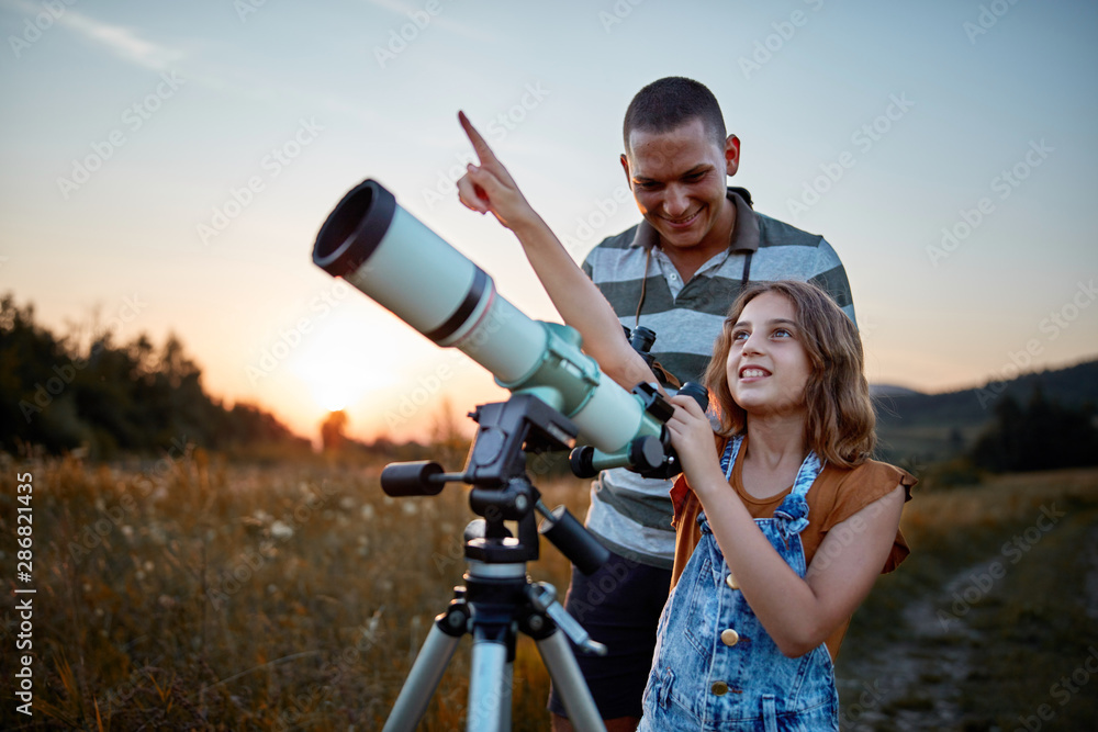 Fototapety, obrazy: Father and daughter observing the sky with a telescope.