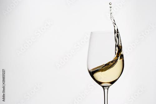 Fotografía  White wine splashing from an elegant wineglass