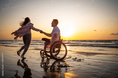 Photo Handicapped man in wheelchair and his girlfriend on a beach at sunset