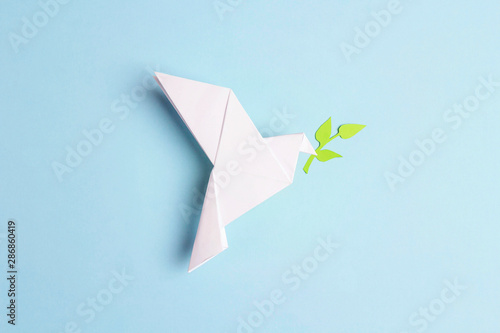 Fotografering Paper origami dove of peace with olive branch on a blue background
