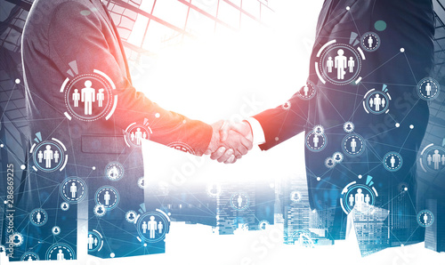 Businessmen shaking hands in city, social network - 286869225