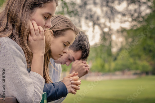 Fototapeta Christian worship and praise. Happy friends praying together in the park. obraz