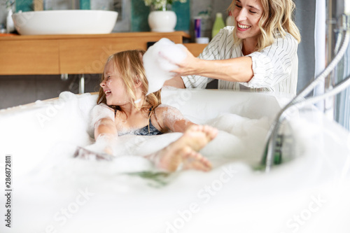 Fotografering Cute girl is squinting eyes in the bath