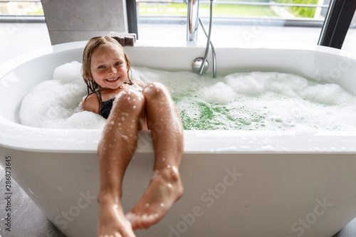 Smiling girl putting her feet on the bath Wallpaper Mural