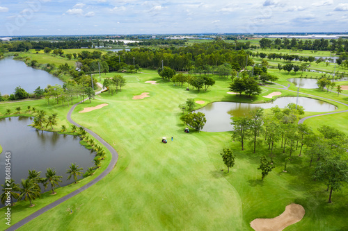 Fotomural  Aerial view of pound on golf course with player, footpath on golf course, playr enjoying the game under sun, golf field