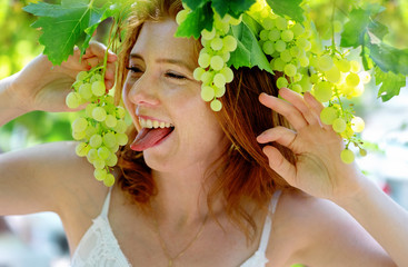 naughty sexy redhead woman sticks out her tongue while eating green grapes