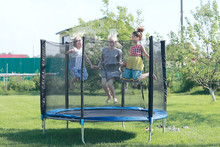 Children Jumping On A Trampoline, Girlfriends Having Fun In The Summer In A Recreation Park On A Trampoline