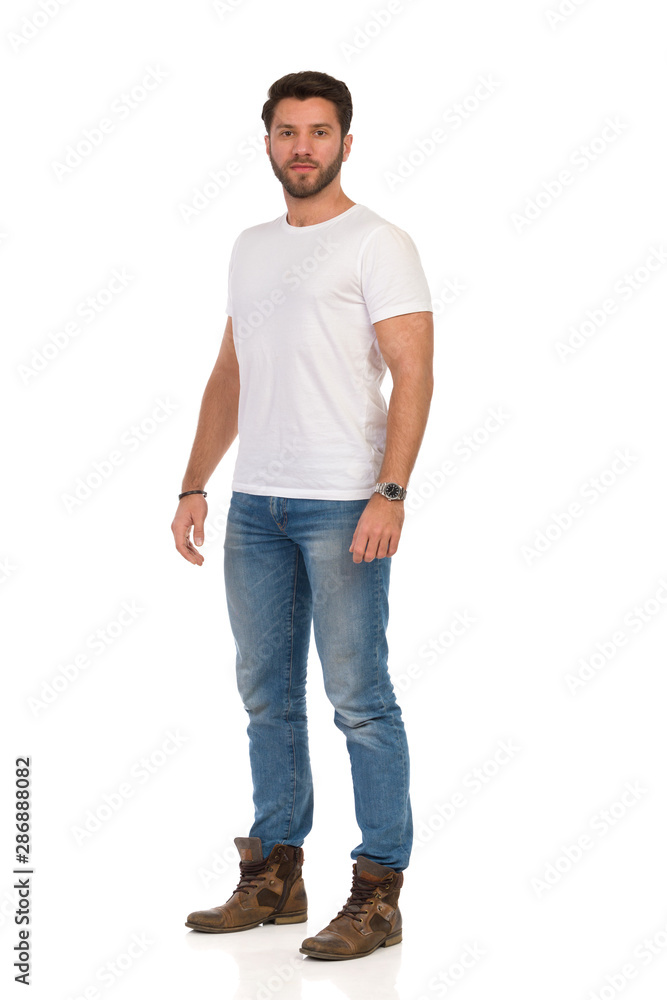 Fototapeta young man standing with his hands in pockets