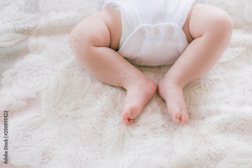 Fotografía  Little legs of a baby lying on a white bed at home