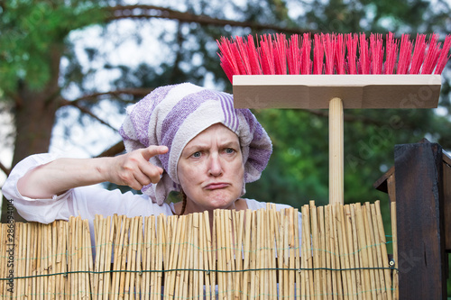 Fotografía  An aggressive, elderly woman with a headscarf and broom scolds at the garden fence