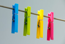 Four Colorful Clothespins (yellow, Green, Blue And Pink) Hanging On The Clothesline.