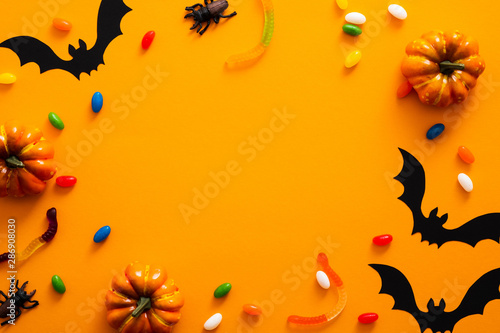 Happy halloween holiday concept. Halloween decorations, pumpkins, bats, candy, bugs on orange background. Halloween party greeting card mockup with copy space. Flat lay, top view, overhead.