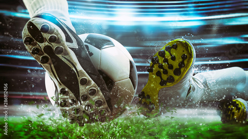 Football scene at night match with close up of a soccer shoe hitting the ball wi Tableau sur Toile
