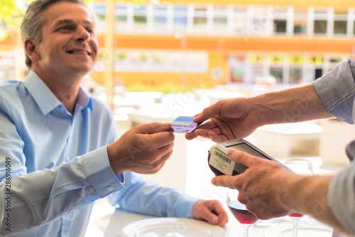 Fototapety, obrazy: Smiling mature customer paying through credit card at restaurant