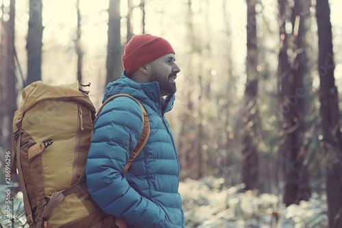 Obraz na plátne  man in sports down jacket landscape winter trekking / down jacket on a tourist,