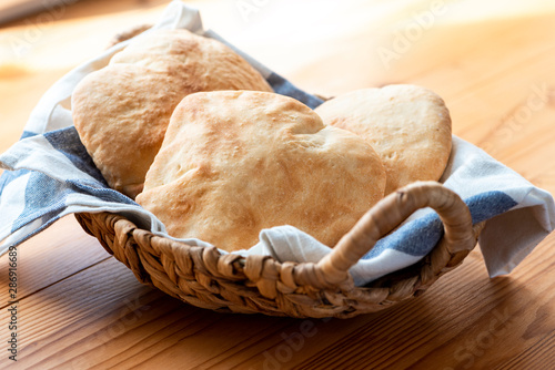 Freshly baked pita in a basket on the table, Arab or Mediterranean cuisine.