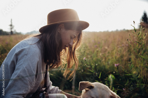 Girl and her friend dog are playing on the straw field background. Beautiful young woman relaxed and carefree enjoying a summer sunset with her lovely dog - 286928056