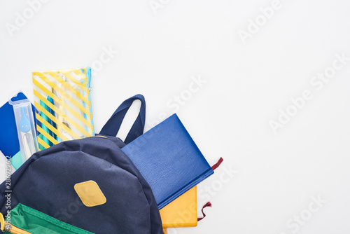 Blue schoolbag with notepads, pencil case and school supplies isolated on white Wallpaper Mural