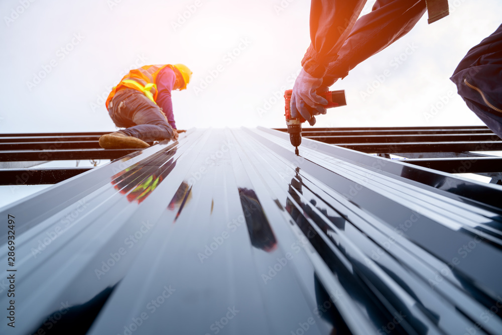 Fototapety, obrazy: Roofer worker in protective uniform wear and gloves, using air or pneumatic nail gun and installing asphalt shingle on top of the new roof,Concept of residential building under construction.