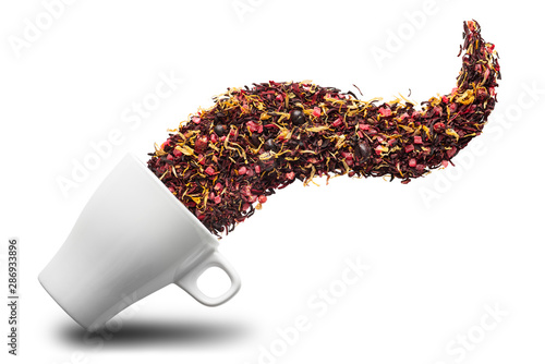 Obraz Dry herbal tea pouring into cup isolated on white background. Flat lay. Abstract concept. - fototapety do salonu