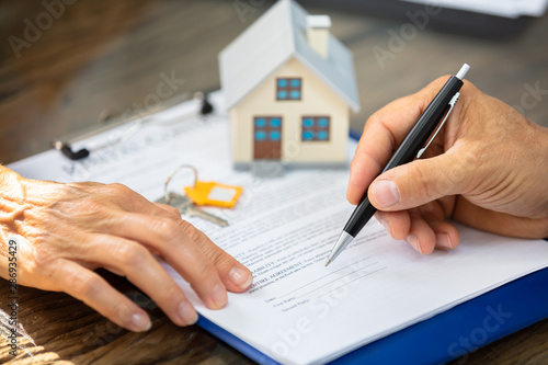 Fototapeta Real Estate Agent Helping Client In Filling Contract Form obraz