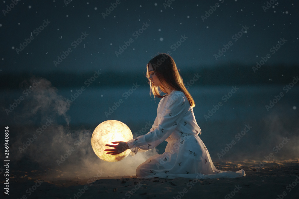 Fototapeta Beautiful attractive girl on a night beach with sand and stars hugs the moon,