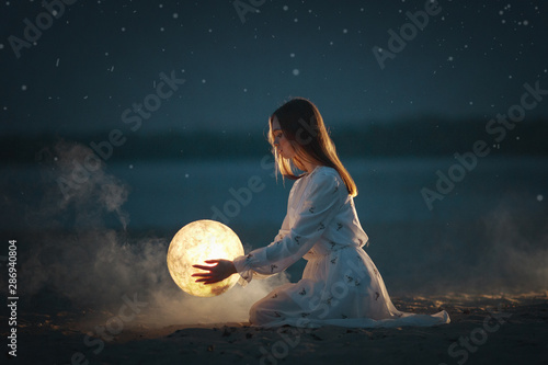 Fototapeta Beautiful attractive girl on a night beach with sand and stars hugs the moon, obraz