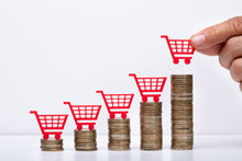 Businessman With Shopping Cart And Coin Stacks In Office