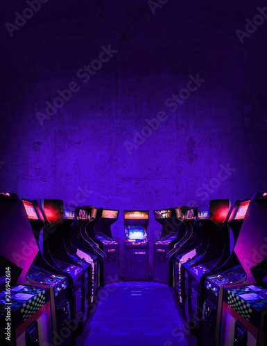 Old Unbranded Vintage Arcade Video Games in dark gaming room with purple light w Fototapete