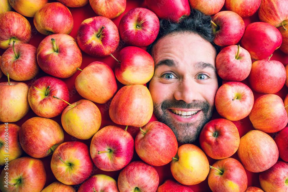 Fototapeta Mann mit Äpfeln, Konzept für die Lebensmittelindustrie. Gesicht von lachenden Frauen in der apffel oberfläche kein Plastikkonzept verpackung