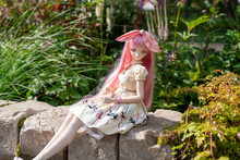 Japanese  Doll On The Bench    In  The  Garden
