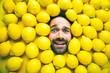 canvas print picture - Mann mit Zitrone, Konzept für die Lebensmittelindustrie. Gesicht vom lachenden mann in der Zitronenoberfläche. Kein Kunststoffverpackungs konzept
