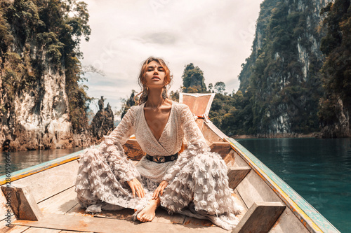 Obraz na plátně  fashionable young model in elegant dress on boat at the lake
