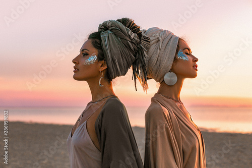 Fotografie, Obraz two young beautiful girls in turban on the beach at sunset