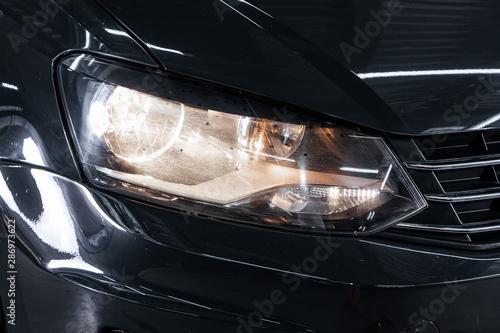 Obraz Black car headlights. Exterior detail. Close up detail on one of the LED headlights modern car.. - fototapety do salonu