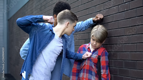 Cruel students threatening to punch junior boy, school bullying, intimidation Fototapet