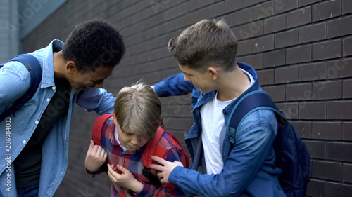 Cruel teenagers punching younger boy, physical intimidation, school bullying Canvas-taulu