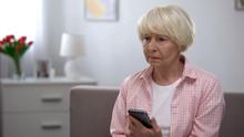 Depressed Elderly Woman Holdin...