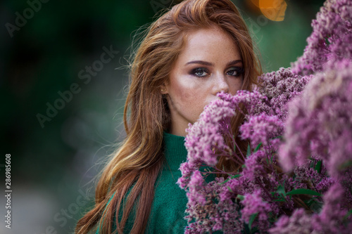 Canvas Print Sunshine young smiling woman with red curly hair is wearing green sweater and hat in autumn park near purple bush of flowers