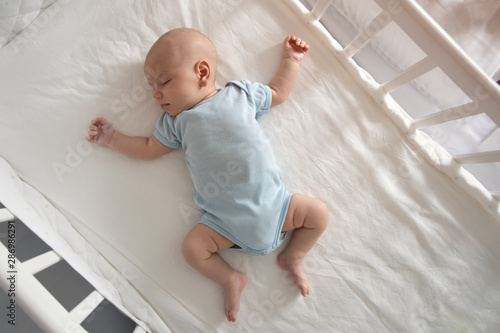 Top view wide angle sleeping newborn baby lies in a crib arms and legs outstretc Fototapeta