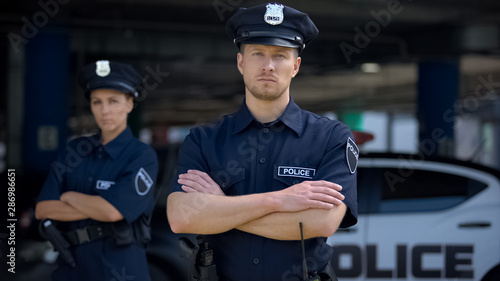 Obraz na plátně Confident male and female police officers in uniform standing near patrol car