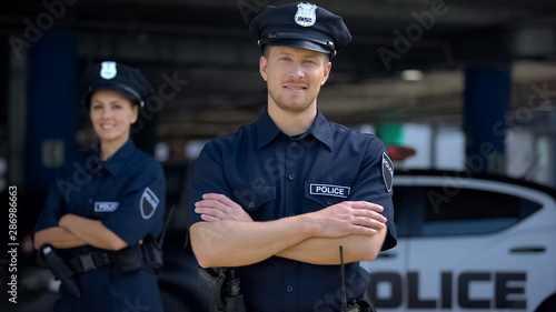 Fototapeta Kind police officers smiling standing near police station, ready to help, order