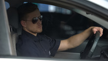 Confident Policeman Sitting In Patrol Car And Wearing Sunglasses, Ready For Work