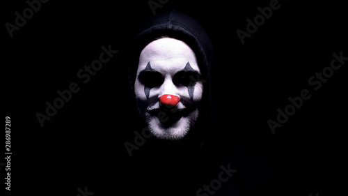 Maniac with spooky clown face angrily smiling into camera, psycho threatening Canvas Print