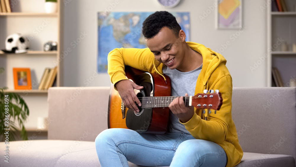 Fototapety, obrazy: Happy African-American teenager playing guitar, enjoying favorite hobby, leisure