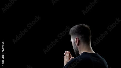 Fotomural Praying man on black background, sins forgiveness, spiritual inspiration, help
