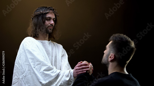 Son of God holding hands of praying man, spiritual support, absolution of sins Wallpaper Mural