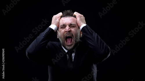 Worried businessman shouting on dark background, mental exhaustion, pressure Wallpaper Mural