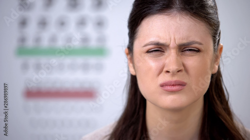 Lady patient with myopia squeezing eyes and feeling depressed, sight correction