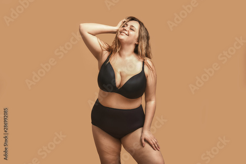 Beautiful and happy plus size woman in black underwear keeping eyes closed and s Tablou Canvas